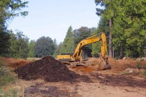 Yellow tractor beside a stockpile of soil - Big Easy Demolition