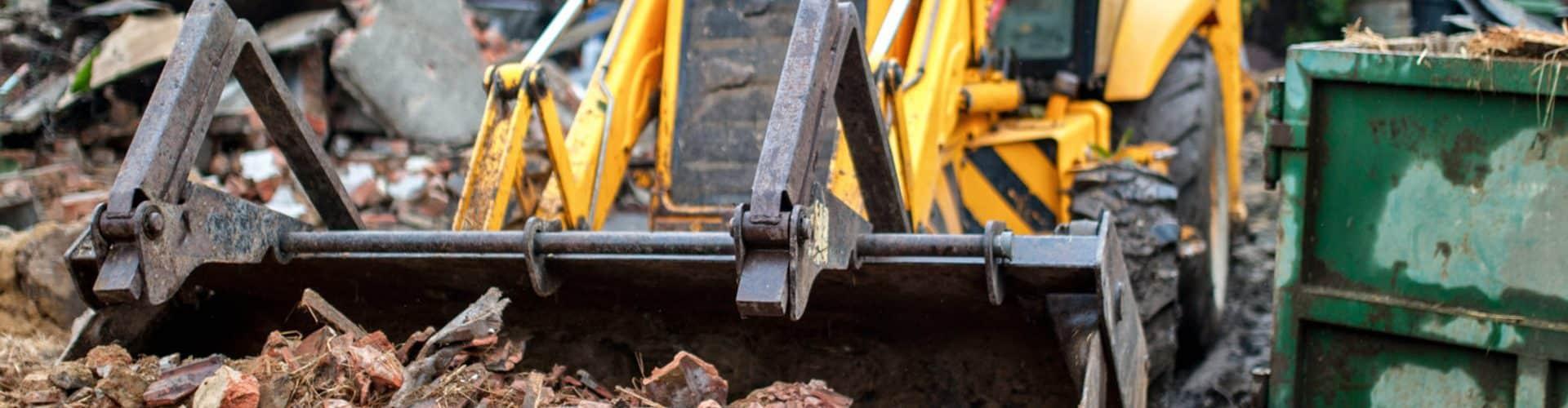 Bulldozer gathering debris from a house - Big Easy Demolition