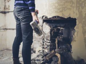 a woman demolishing a wall with a hammer - Big Easy Demolition