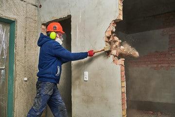 a man demolishing a wall by a hammer - Big Easy Demolition