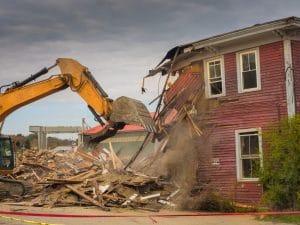 Backhoe Demolishing a Residential House