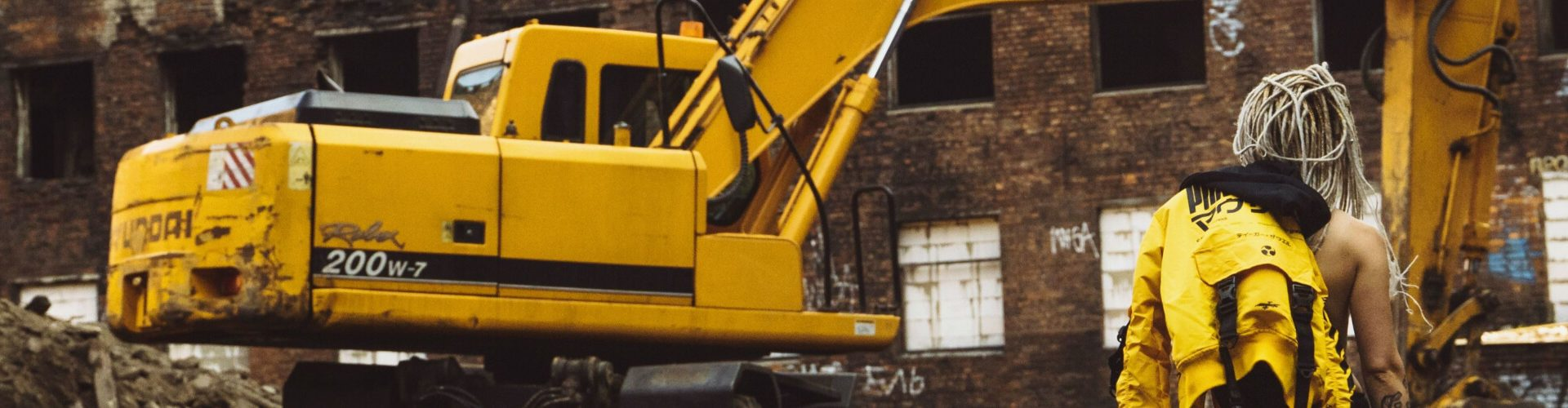 man standing in front of a backhoe