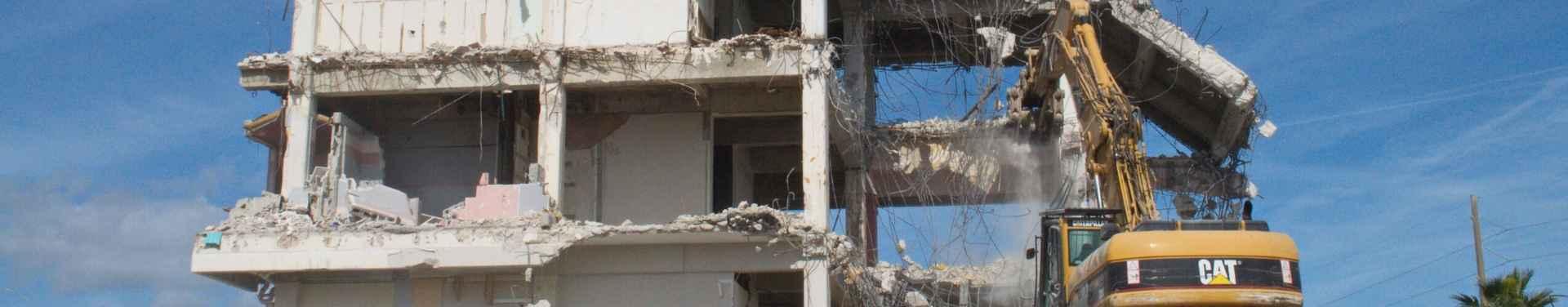 backhoe demolishing a commercial building